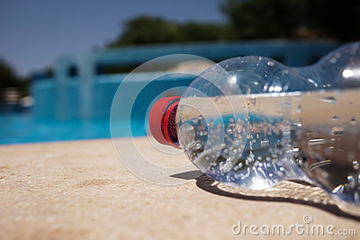 Flaska av vatten på poolside