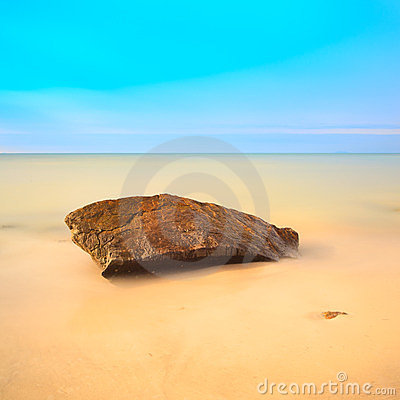 Flat rock on a golden beach. Long exposure.