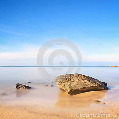 Flat rock on golden beach and sea. Long exposure.