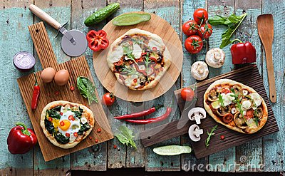Flatlay of pizza party. Homemade pizzas and raw vegetables in ab Stock Photo