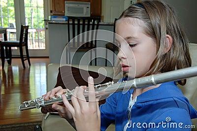 Flauta practicante de la muchacha en el país