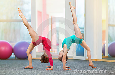 Flexible Kids Gymnasts Doing Acrobatic Exercise In Gym