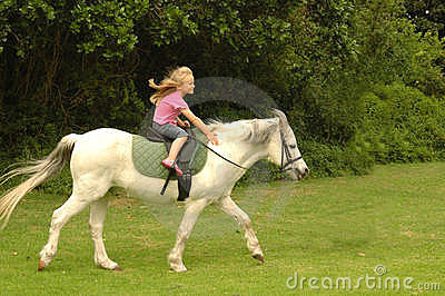 Flicka henne ponnyridning