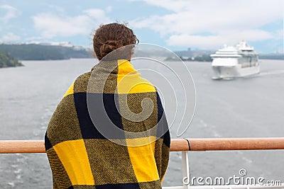 Flicka i pläd på däck av shipen