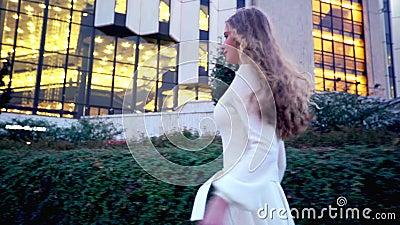 Flicka med långa körningar för blont hår på den utomhus- aftongatan arkivfilmer