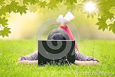 Flicka som ligger på gräs genom att använda den utomhus- bärbara datorn