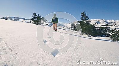 Flickalopp som fotvandrar i vinterberg, fotspår i snön, ultrarapid arkivfilmer