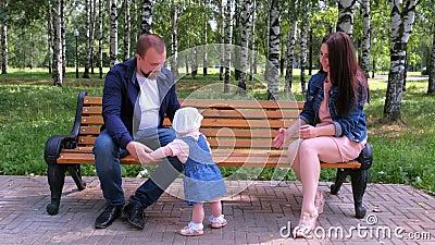Flickan försöker ta första steget från mamma till pappa som sitter på bänk i parken stock video