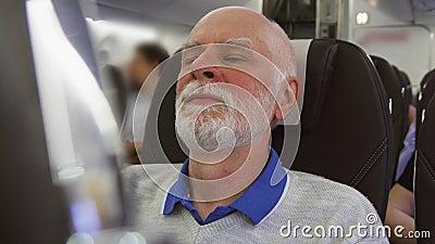 Fliegen des älteren Mannes im Flugzeug in der Tageszeit Ermüdet durch männliches entspannendes nahes Fenster des Jetlags während  stock footage