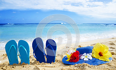 Flip flops and hat with tropical flowers on sandy beach