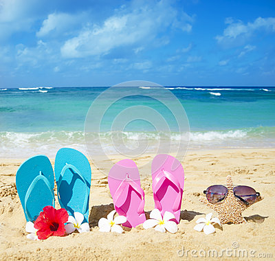 Flip flops and starfish with sunglasses on sandy beach