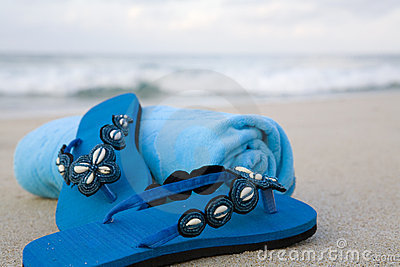 Flip flops and towel on a beach