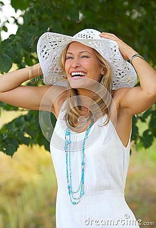 Flirtatious portrait of a girl with a summer hat