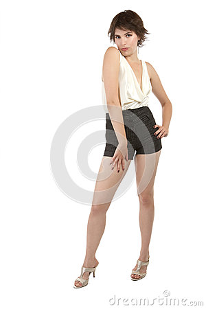 Flirtatious young woman stands with hand on hip
