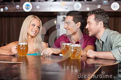 Flirting at the bar. Two cheerful young men and beautiful young