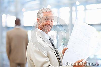 Fälliger Architekt, der eine Lichtpause studiert