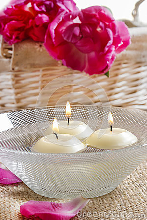 Floating candles in water among rose petals