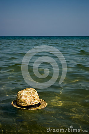Boater hat floating on the water as holiday concep