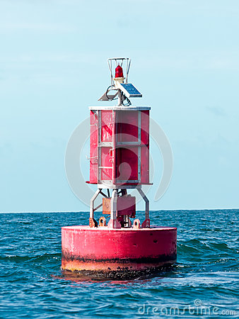 Floating red buoy at mid of sea