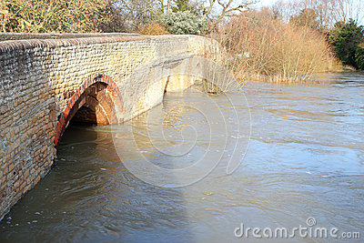 Flood water under a stone bridge.