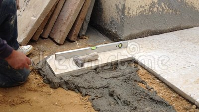 Flooring with cement outdoor. A construction worker fixing tiles of floor with cement outdoor stock footage