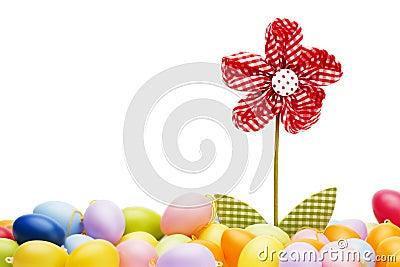 Flor roja de la pañería entre los huevos de Pascua