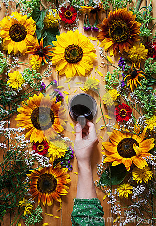 Free Floral Summer Background. A Mug Of Coffee In A Woman`s Hand On A Wooden Background With Sunflowers And Wildflowers Royalty Free Stock Photography - 95790117