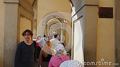 Florence Italien, Juni, 2017: En grupp av turister med en handbok går vidare den berömda bron över Arno River i Florence arkivfilmer