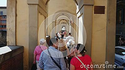 Florence Italien, Juni, 2017: En stor grupp av turister med en handbok går vidare den berömda bron över Arno River in arkivfilmer