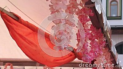 Flores artificiais, cor-de-rosa e delicadas, decoração de flores falsas, balançando ao vento num festival de férias vídeos de arquivo