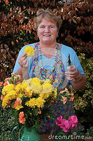Flores de trabajo de la señora madura fuera del retrato