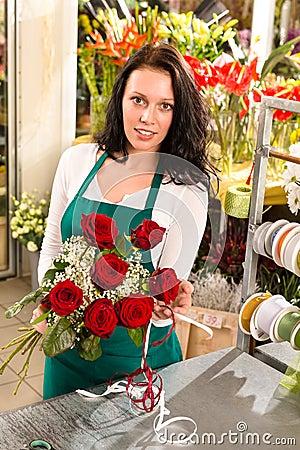 Florist woman arranging flowers roses shop working