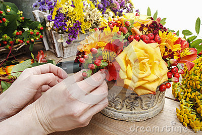 Florist at work: woman making bouquet of orange roses and autumn