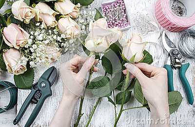 Florist at work. Woman making bouquet of pink roses.