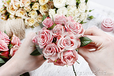 Florist at work. Woman making bouquet of pink roses
