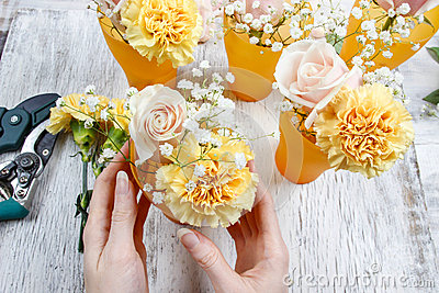 Florist at work. Woman making bouquet of pink roses and yellow c