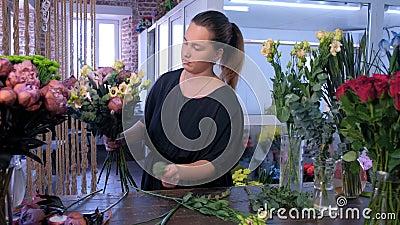 Floriste crée un bouquet d'eucalyptus, d'eustome, de pivoine et d'iris dans un fleuriste banque de vidéos