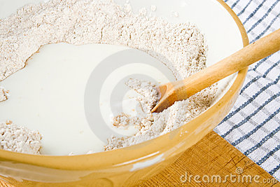 Flour, milk and a spoon in a bowl