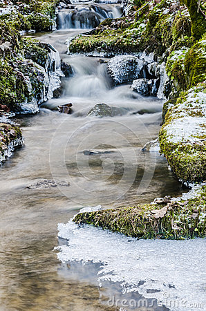 Flow of water in the spring of icicles and ice Stock Photo