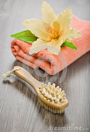 Flower on pink towel with massager and brush