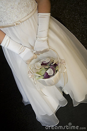 Flowergirl holding basket with petals in it