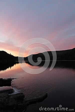 Flowing river reservoir with small waterfall at sunset.Peak district. Derwent Valley.