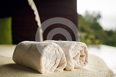 Fluffy towels and seashells on beach table