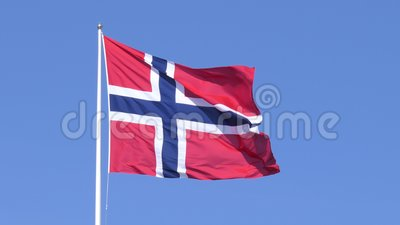 Fluttering Norwegian flag. A Norwegian flag fluttering in the wind, set against a clear blue sky stock footage