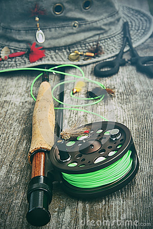 Fly fishing reel with old hat on bench