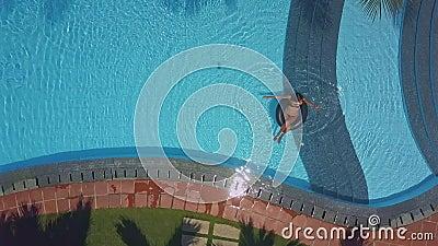 Flycam mostra lo stagno dell'hotel con signora che si siede sulla boa video d archivio