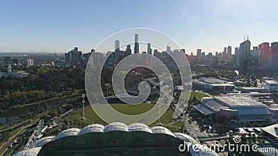 Flyg- pullback sköt av i stadens centrum panorama för den Melbourne staden och Melbourne rektangulär stadion, Melbourne, Victoria lager videofilmer