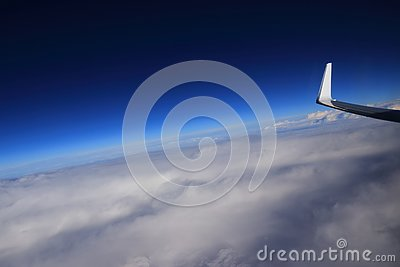 Airplane wing tip flying above clouds blue sky