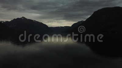 Flying over water in the rain. Soothing and slow drone aerial shot flying over a body of water in rain and dusk. Perfect for intros, outtros and backgrounds stock footage