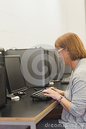 Focused mature student sitting in computer class